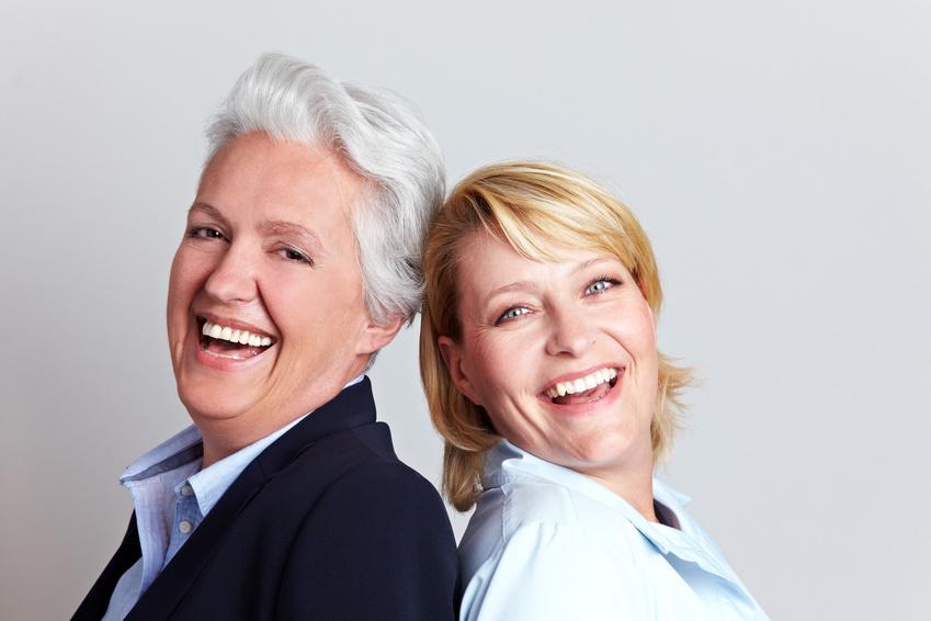 Lachende Seniorin und ihre Tochter lehnen sich an